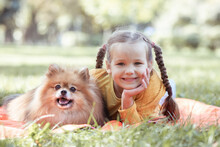 A Girl And A Spitz Dog, A Child Sits In The Park On An Orange Blanket, A Fluffy Spitz Dog Sits Next To The Girl, A Baby Smiles, A Portrait Of A Child And An Animal.