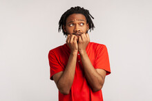 Anxious Man With Dreadlocks Wearing Red Casual Style T-shirt, Biting Nails On Fingers Looking At Away With Terrified Expression, Confused And Worried. Indoor Studio Shot Isolated On Gray Background.