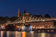 The Illuminated Footbridge Called Eiserner Steg Which Crosses The River Main In Frankfurt, Germany, At Night