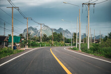 Asphalt Road With Mountain Range And Utility Pole And Lamppost In Countryside At Sam Roi Yot