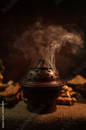 Fototapeta Burning incense in a traditional pottery pot