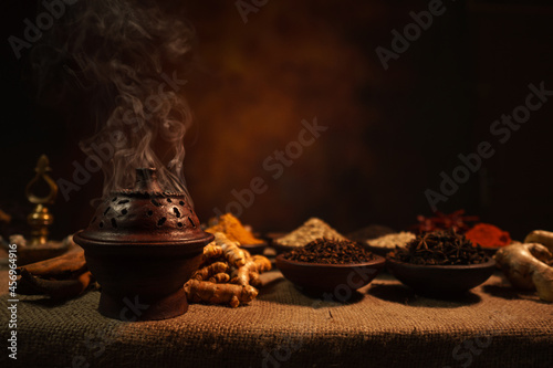 Fotografie, Obraz Burning incense in a traditional pottery pot on a blurred spice background