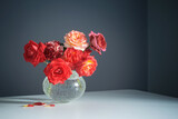 red  roses in white vase on gray background
