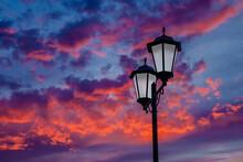 Vintage Streetlight Against The Sky Background. Sun Rays Creating An Unusual Sky