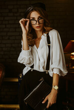 Elegant Lady Wearing Trendy Glasses, White Shirt, Black Beret, Suspenders, Trousers, Golden Wrist Watch, Holding Leather Bag, Posing In Vintage Dark Interior. Copy, Empty Space For Text