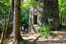 A Stone Cylinder Shaped Building In The Forest Covered With Colorful Graffiti Surrounded By Lush Green Trees At Lullwater Preserve In Decatur Georgia
