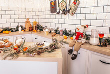 Christmas Beautiful Decorated Kitchen Interior New Year Snowman Toy Sitting On Wooden Table Utensils Green Tree Branch Products Tangerines, Copy Space Bakery Marshmallows