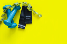 A Black Fitness Elastic Band And Two Blue Dumbbells Lie On A Yellow Background, A Measuring Tape Lies Above Them In Rings. Top View, Flat Lay, Copy Space, Isolate.