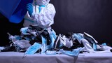 Recycle worker in gloves, sorting medical masks in the recycle bin. Depiction of recycle plant facility. Pollution by surgical masks in coronavirus pandemic and harm to environment. Disposable masks.