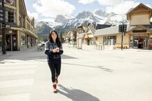 Woman With Digital Camera Walking Down Street In Mountain Resort