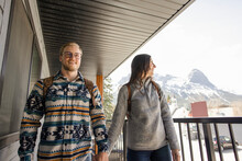 Couple Walking Along Hotel Balcony With Mountain View