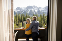 Couple Looking At Mountain View On Hotel Balcony