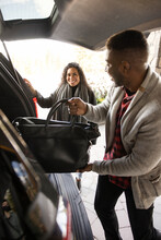 Couple Unpacking Car At Hotel