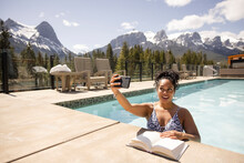Woman Reading Book On Edge Of Pool With Mountain View