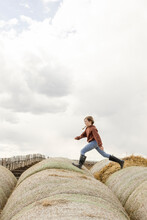 Girl Running And Playing On Rolled Hay Bales On Farm