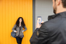 Man Taking Photo Of Woman Standing In Front Of Yellow Panel