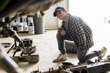 Boy Fixing Machinery In Barn