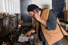 Male Farmer Talking On Smart Phone And Looking In Repair Manual