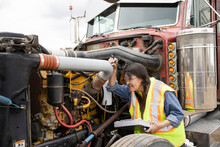 Female Mechanic Inspecting Semi Truck Engine