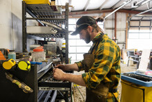Male Bits And Spurs Maker Looking For Tools At Toolbox In Workshop