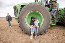 Brother And Sister Using Smart Phone In Wheel Of Tractor On Farm