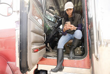 Female Farmer Using Smart Phone In Semi Truck Doorway