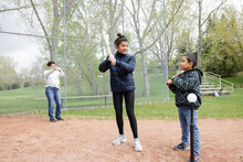 Sister And Brother Practicing Batting On Baseball Field