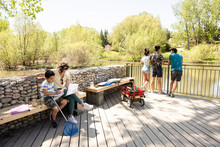Family Learning And Enjoying Nature By Pond