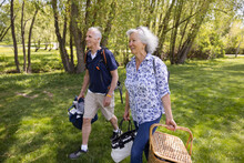 Cheerful Senior Couple Walking With Picnic Basket In Park