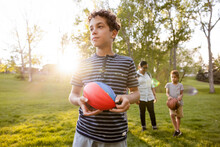 Curious Boy Carrying Colored Ball In Park