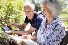 Cheerful Senior Couple Drawing From Phone In Park
