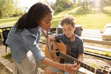 Mother Teaching Son Play Guitar On Park Bench