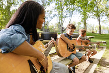 Cheerful Mother Looking At Sons Playing Guitar On Park Bench