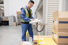 Male Worker With Clipboard In Warehouse