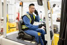 Male Worker Talking On Smart Phone On Forklift