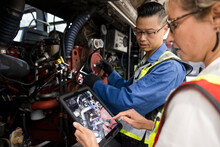 Mechanics With Digital Tablet Fixing Bus Engine