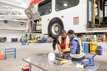 Engineers Working On Bus In Maintenance Facility