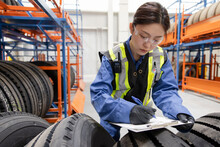 Female Worker With Clipboard Inspecting Tires In Maintenance Facility