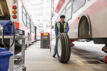 Male Mechanic Replacing Tire On Bus In Maintenance Facility