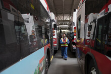 Male Worker Inspecting Buses In Maintenance Facility