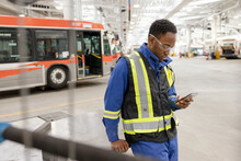 Male Worker With Smart Phone In Bus Maintenance Facility