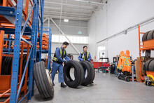 Workers Rolling Tires In Maintenance Facility