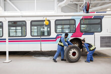 Workers Replacing Tire On Bus In Maintenance Facility