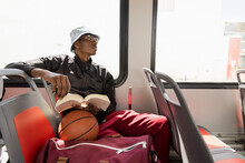 Young Male College Student With Book And Basketball On Sunny Bus