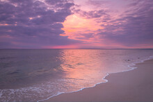 Tropical Pink Sunset Seascape On Cape Cod Beach With Purple Clouds And Gentle White Waves Rolling In On The Pastel-toned Sand