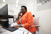 Female Receptionist Answering Telephone In Optometry Center