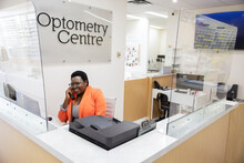 Happy Female Receptionist Answering Telephone In Optometry Center