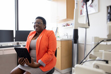 Happy Female Optometrist With Digital Tablet In Exam Room