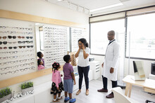Optician Helping Woman With Kids Try On Eyeglasses In Optometry Center