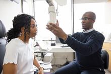 Optometrist Performing Eye Exam On Woman In Optometry Exam Room
